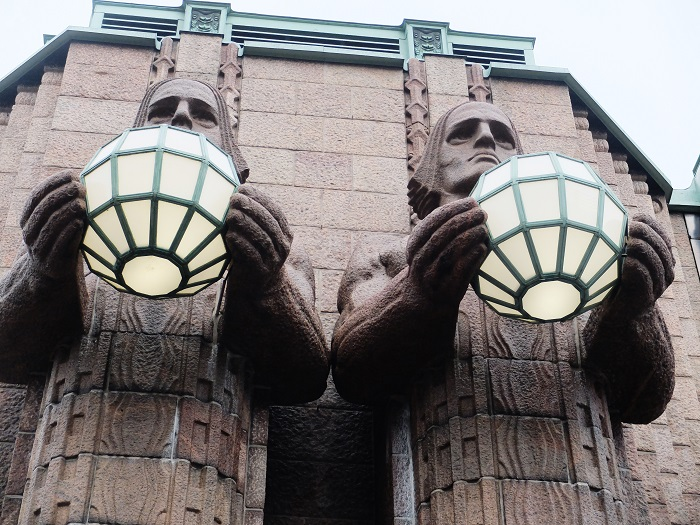 Two statues of mythical giants or gods holding spherical lamps stand welcoming travelers into the station.