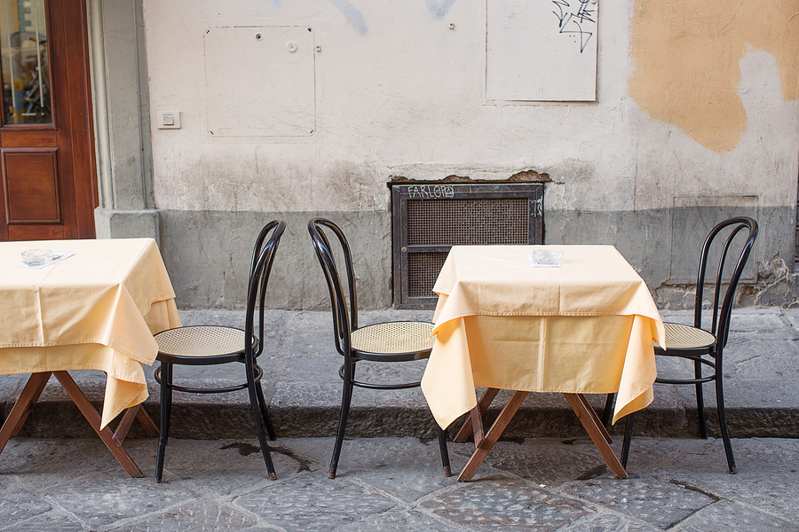 Tables and chairs in the street outside a small cafe near the San Lorenzo leather market florence